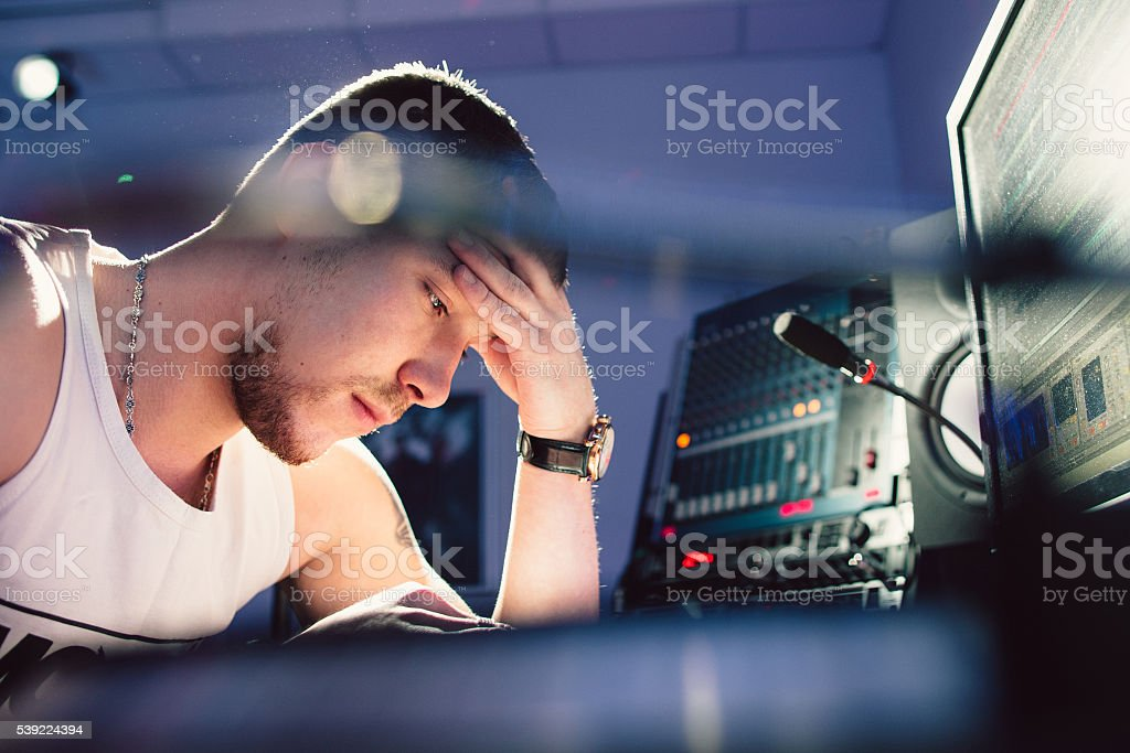 Tired dj sitting at studio close-up stock photo