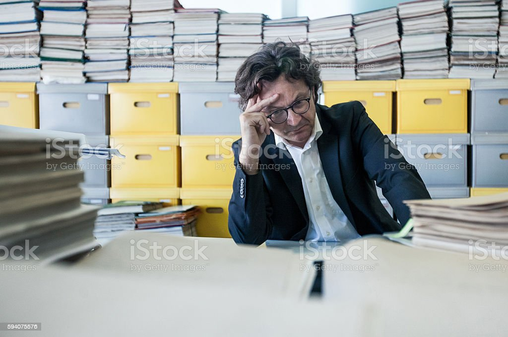Tired  Employee Looking at Paperwork in the Office stock photo