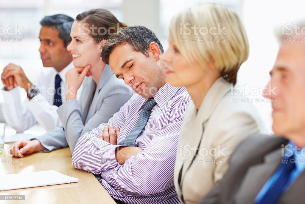 Tired executive falls asleep during a business meeting stock photo