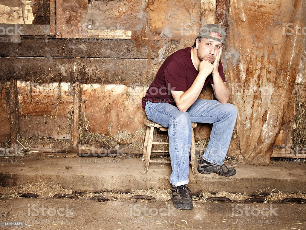 Tired farmer sitting pensively in barn stock photo