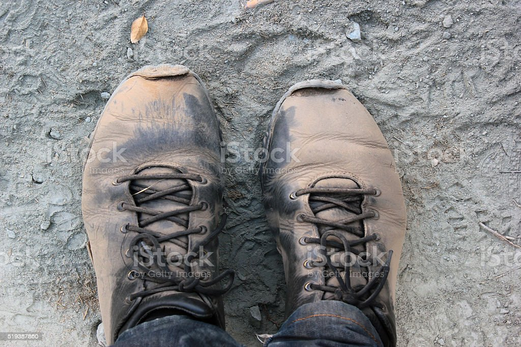 Tired feet in dusty boots stock photo