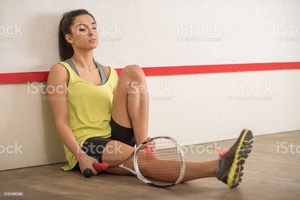 Tired female athlete taking a break from squash game. stock photo