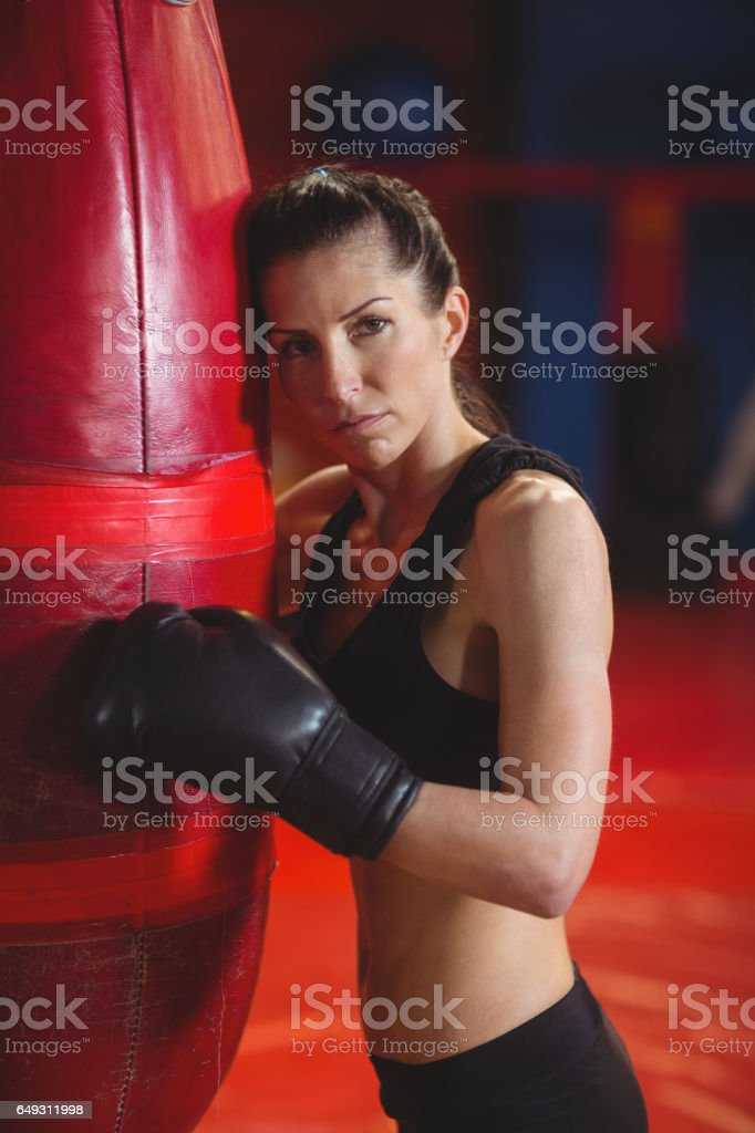 Tired female boxer leaning on punching bag stock photo
