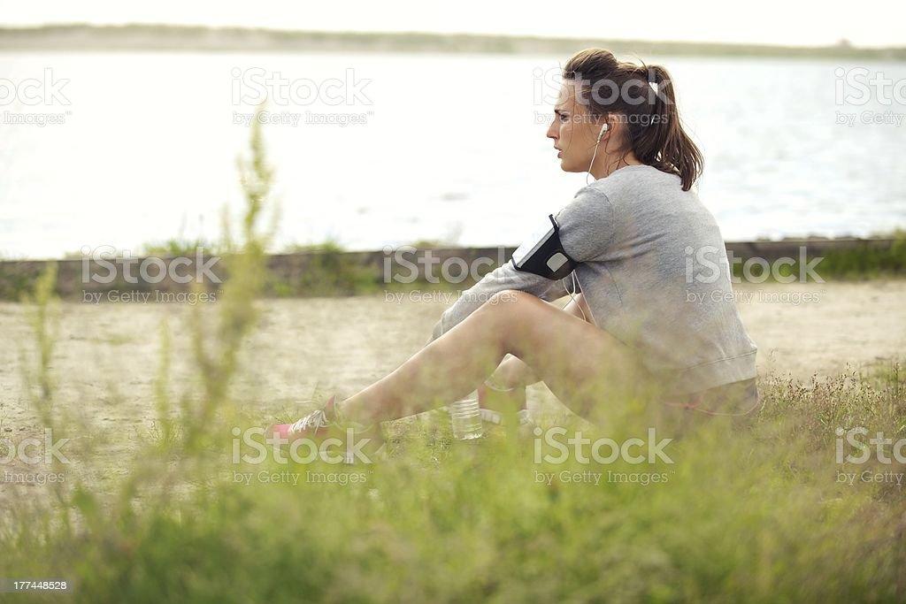 Tired Female Runner Sitting on Grass royalty-free stock photo