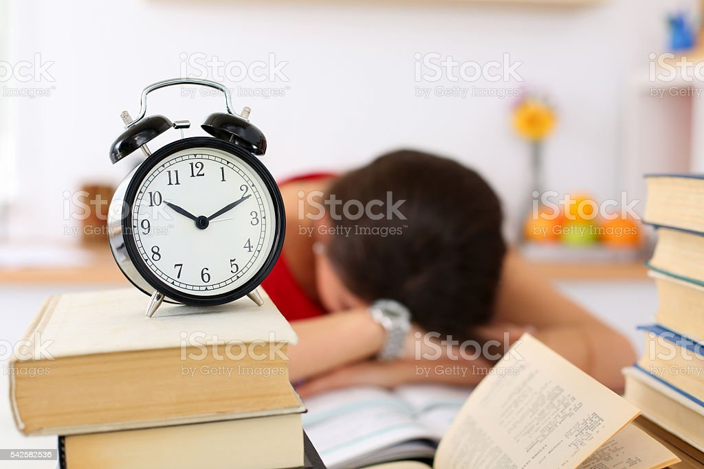 Tired female student at workplace in room taking nap stock photo