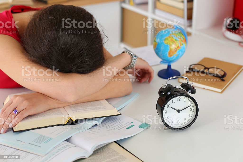 Tired female student at workplace stock photo