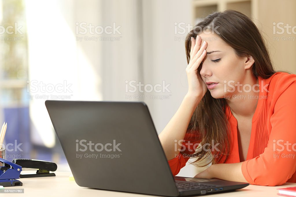 Tired freelancer working with a laptop stock photo