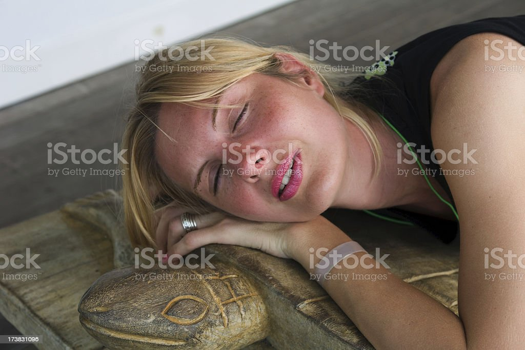 Tired girl deeply asleep on a wooden turtle shaped bench stock photo