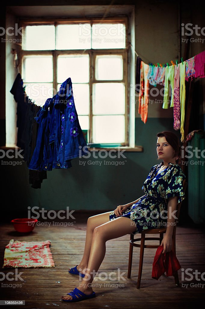 Tired girl sitting on a chair near the washed laundry stock photo