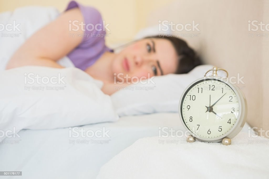Tired girl waking up in her bed stock photo