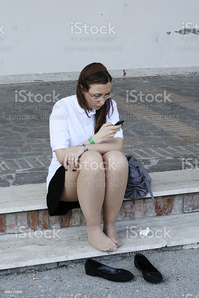 Tired Girl Writing a Message on Cell Phone royalty-free stock photo