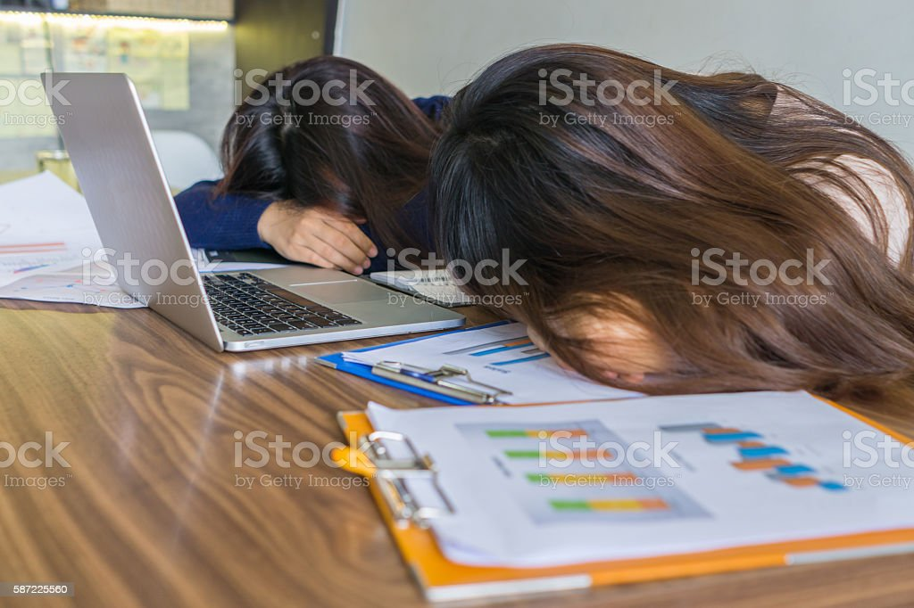 Tired girls lay their face down on desk and document stock photo