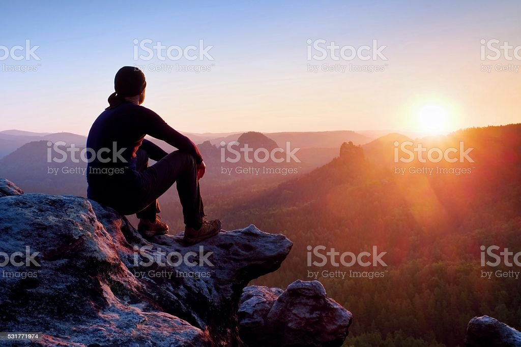 Tired hiker in black trousers, jacket and cap on cliff stock photo