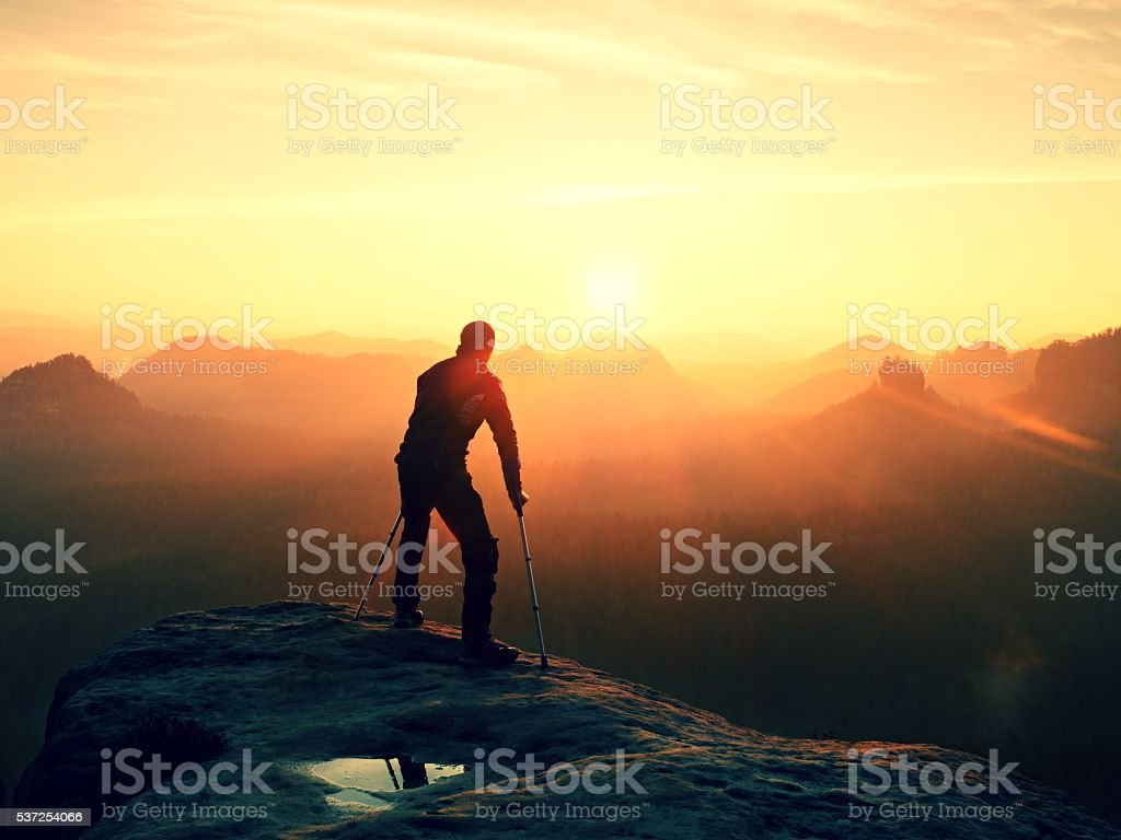 Tired hiker with broken leg in immobilizer walk on rock stock photo