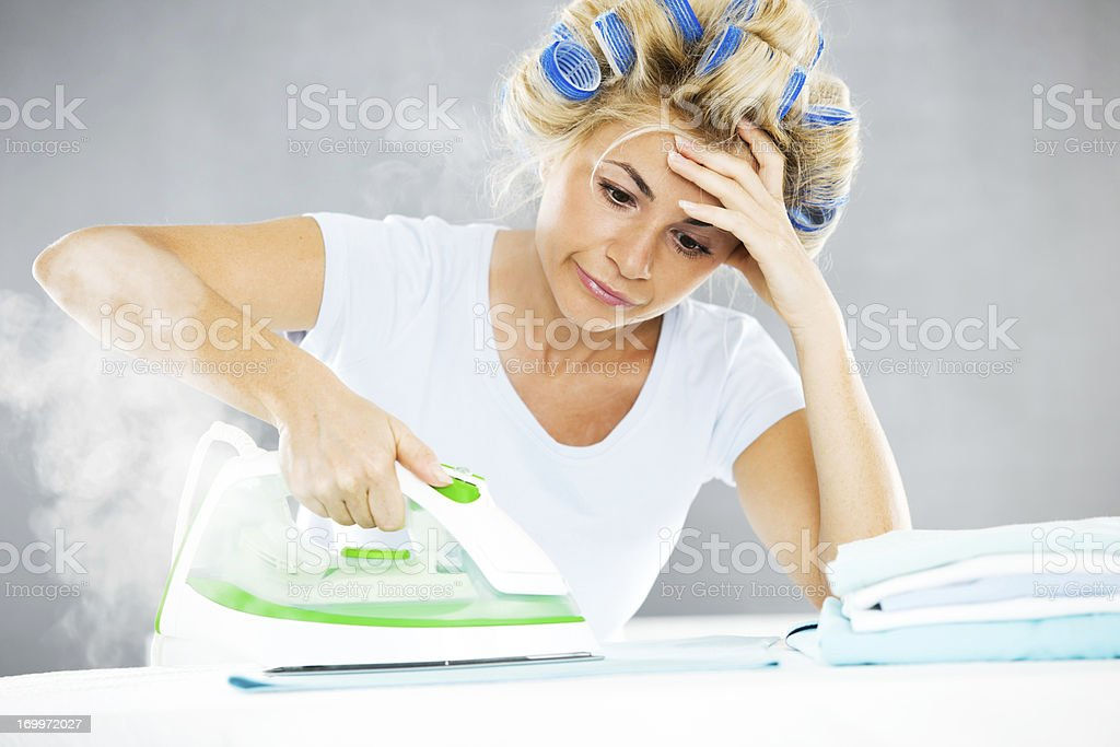 Tired housewife and an iron. stock photo