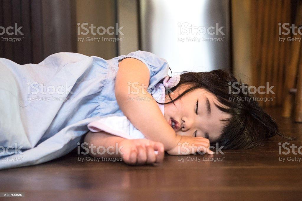 Tired Japanese Toddler Girl Sleeping on Floor at Home stock photo