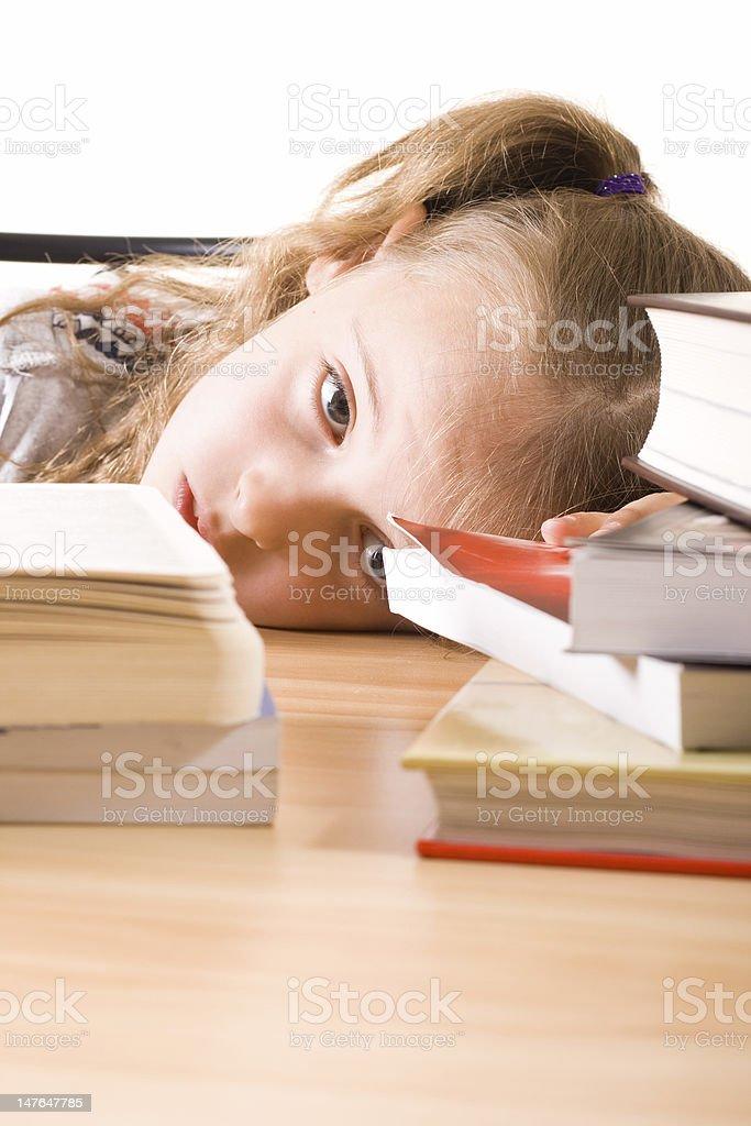 Fatigué petite fille regarde minier des livres photo libre de droits