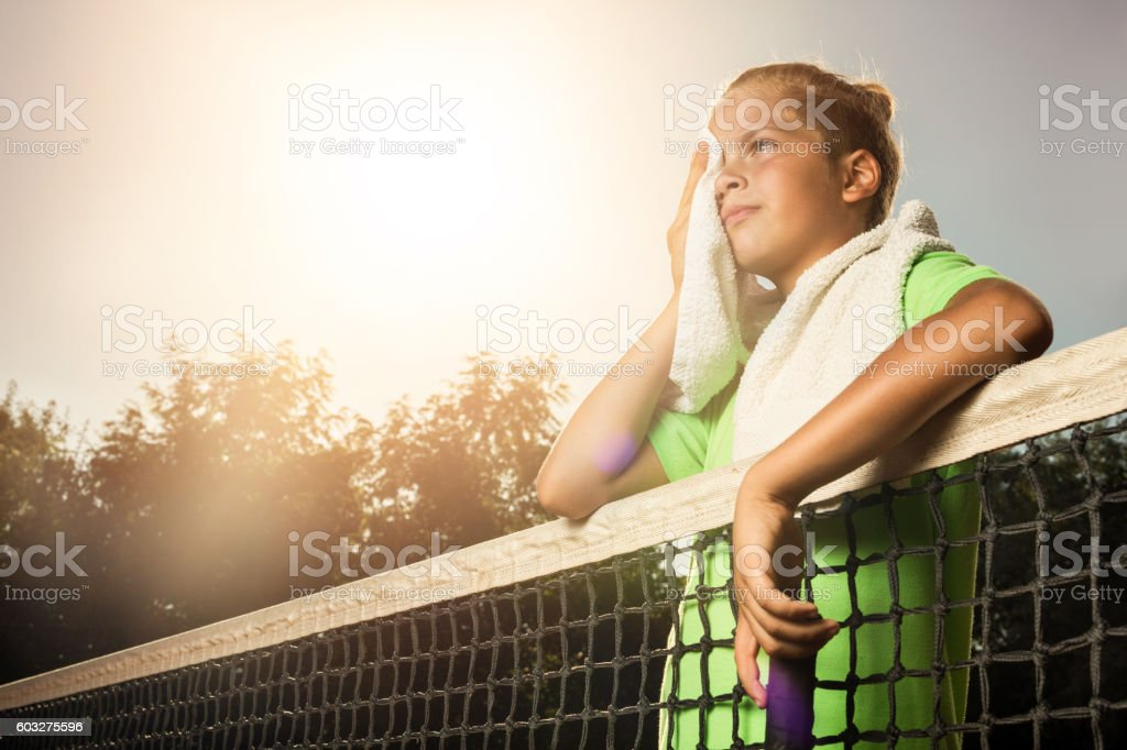Tired little tennis player wiping sweat after sport training. stock photo