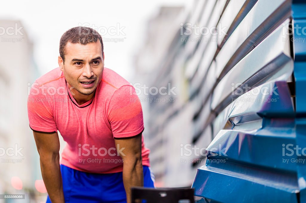 Tired male jogger bending by metal wall stock photo