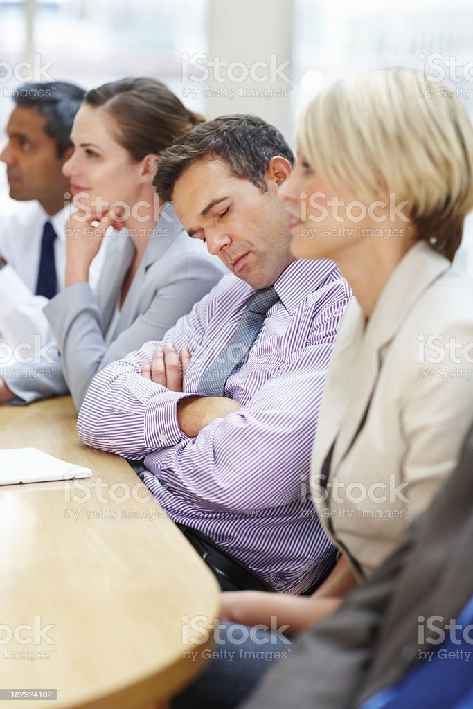 Tired male worker sleeping in a meeting royalty-free stock photo