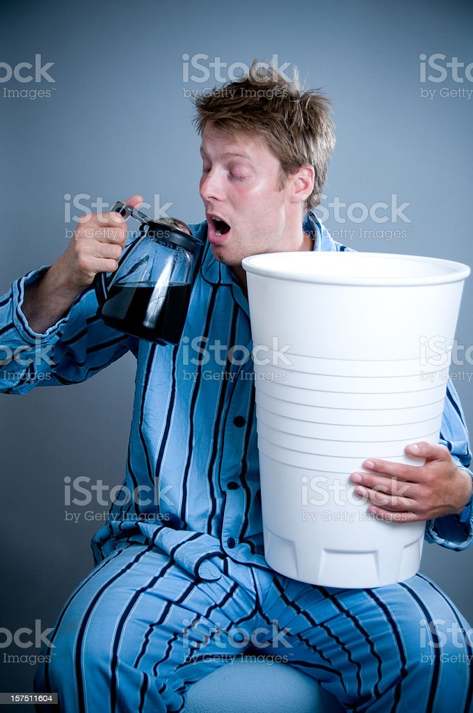 Tired man in pajamas drinks coffee from the can royalty-free stock photo