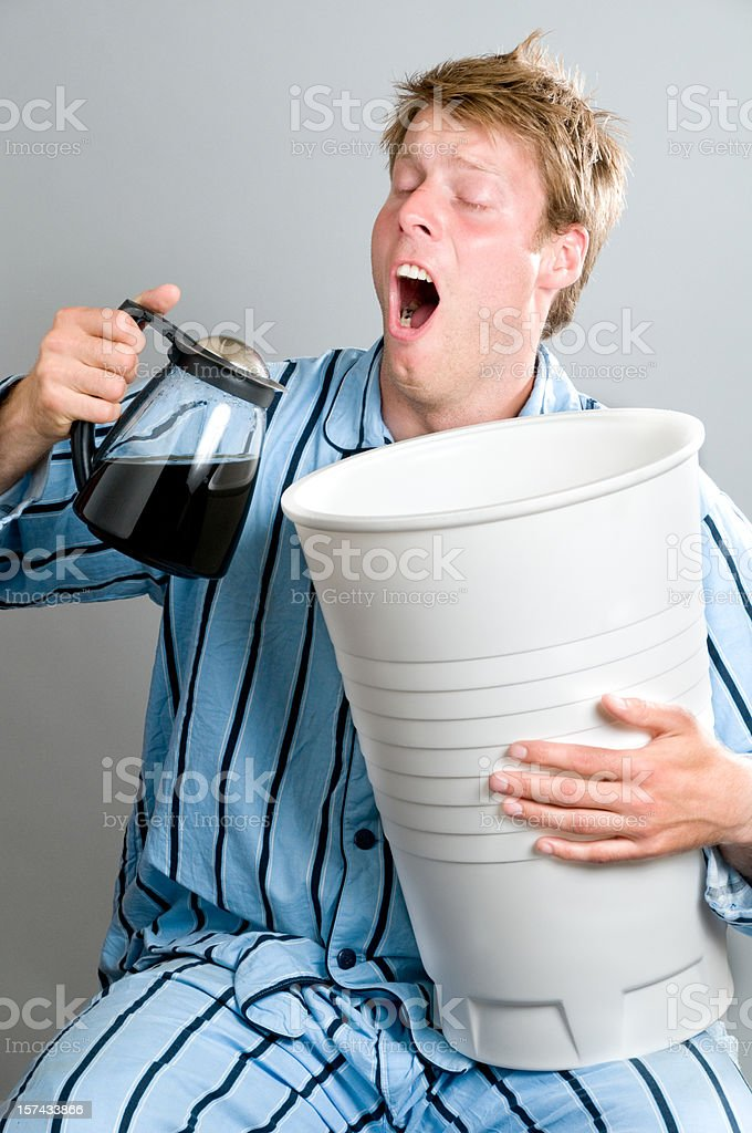 Tired man in pajamas is yawning and pouring coffee royalty-free stock photo