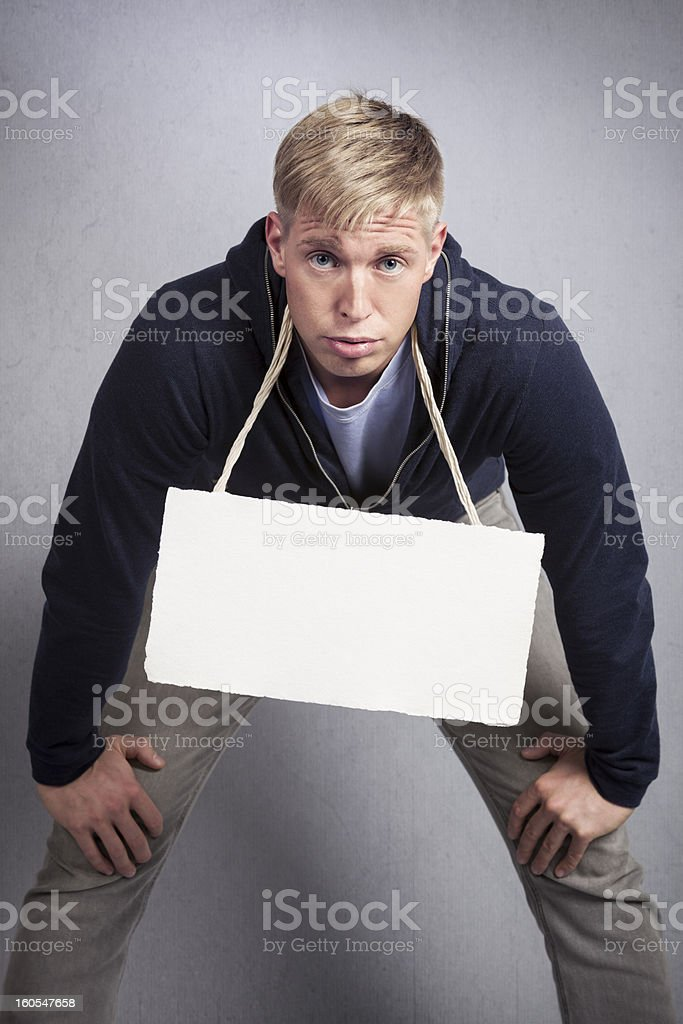 Tired man presenting blank signboard. royalty-free stock photo