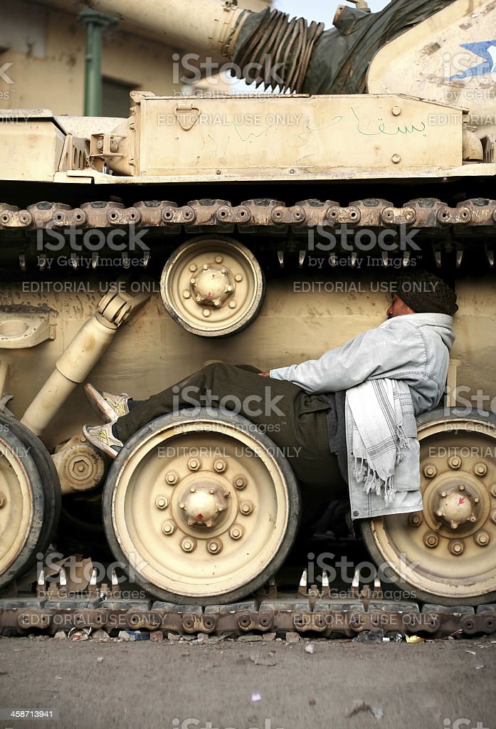 tired man sleeping on tank wheels..Egypt 2011 revolution stock photo
