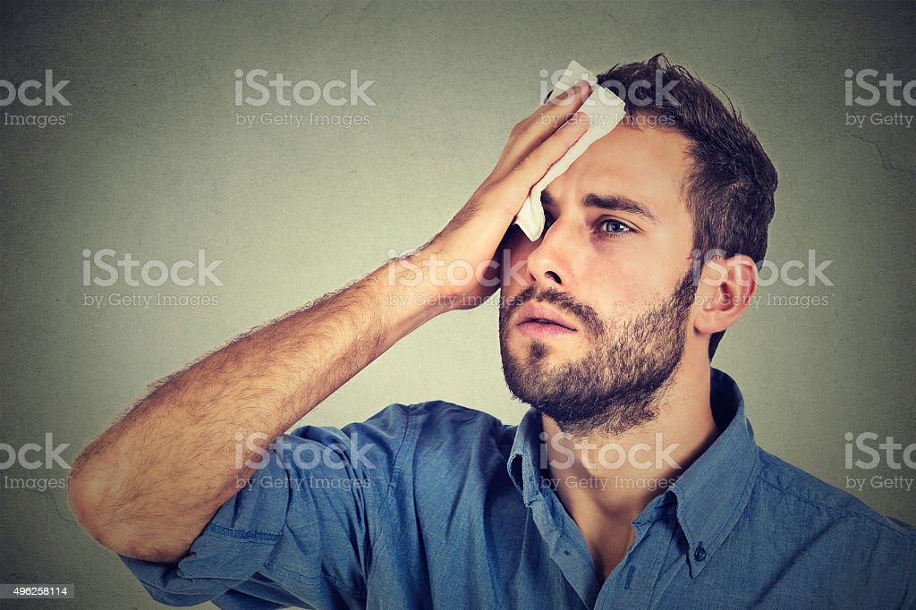 Tired man stressed sweating having fever headache stock photo