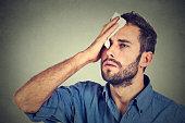 Tired man stressed sweating having fever headache