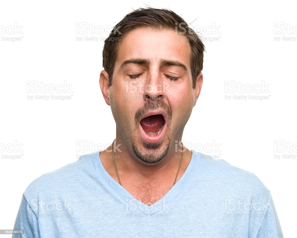 A tired man wearing a blue top is yawning  stock photo