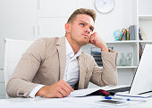 Tired man working in office