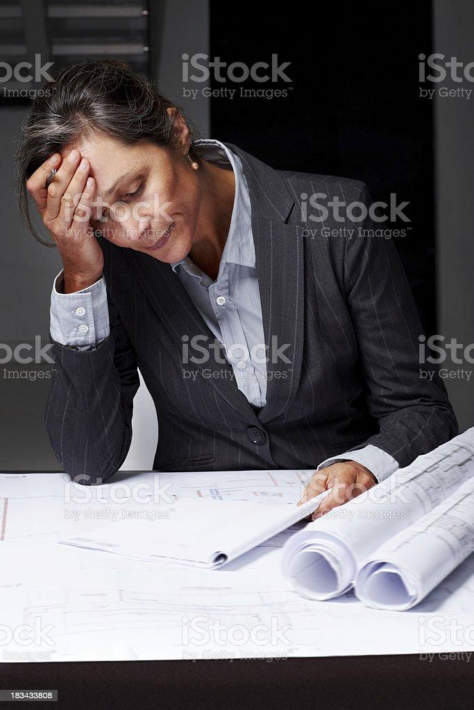 Tired mature female architect working on blueprints royalty-free stock photo