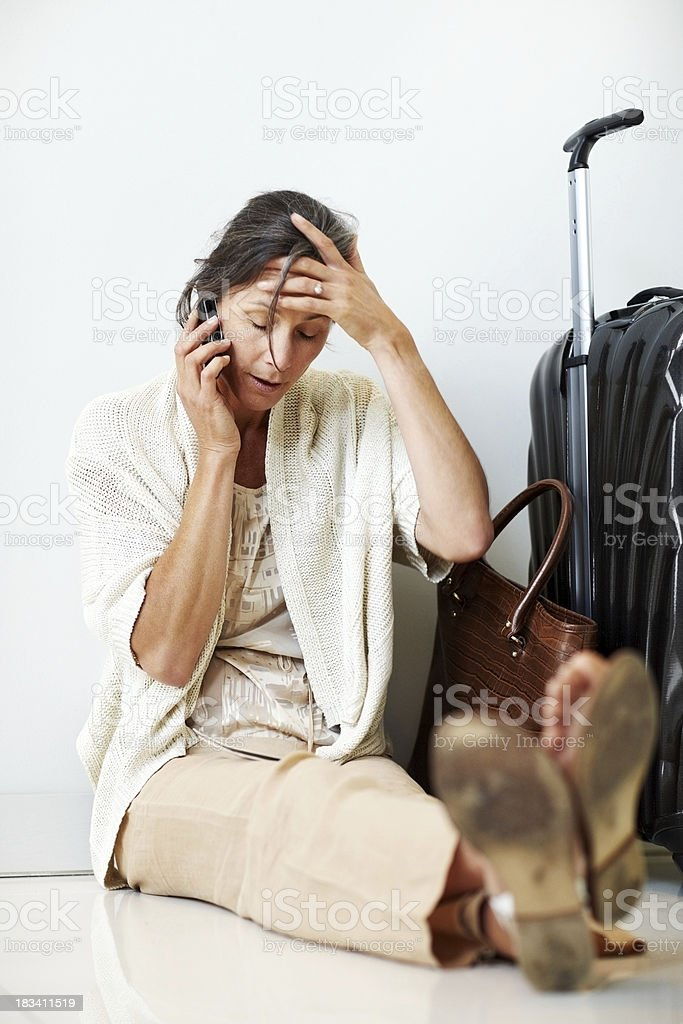 Tired mature woman waiting for a delayed flight royalty-free stock photo