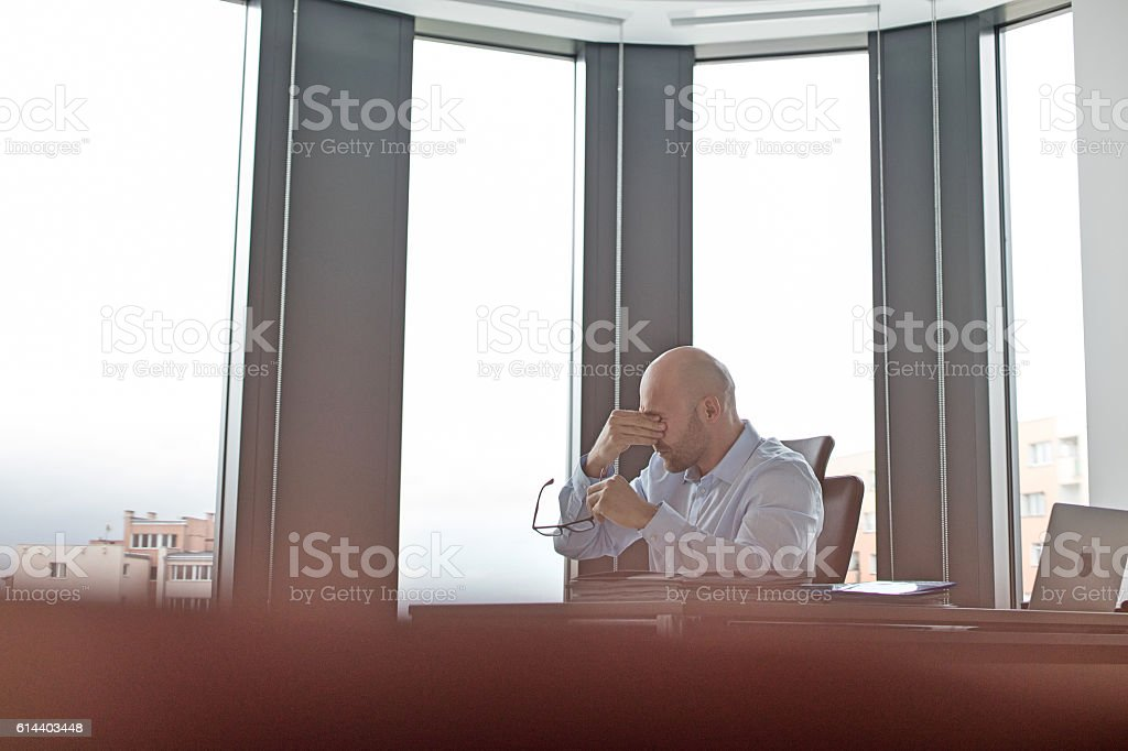 Tired mid adult businessman rubbing eyes in office stock photo