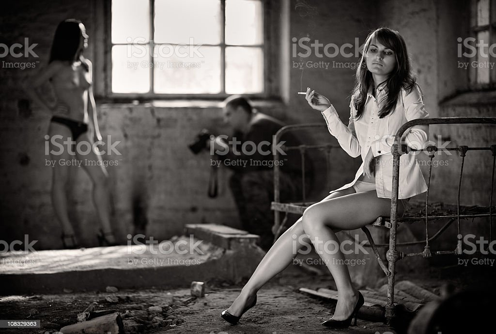Tired model rests while sitting on the old bed royalty-free stock photo