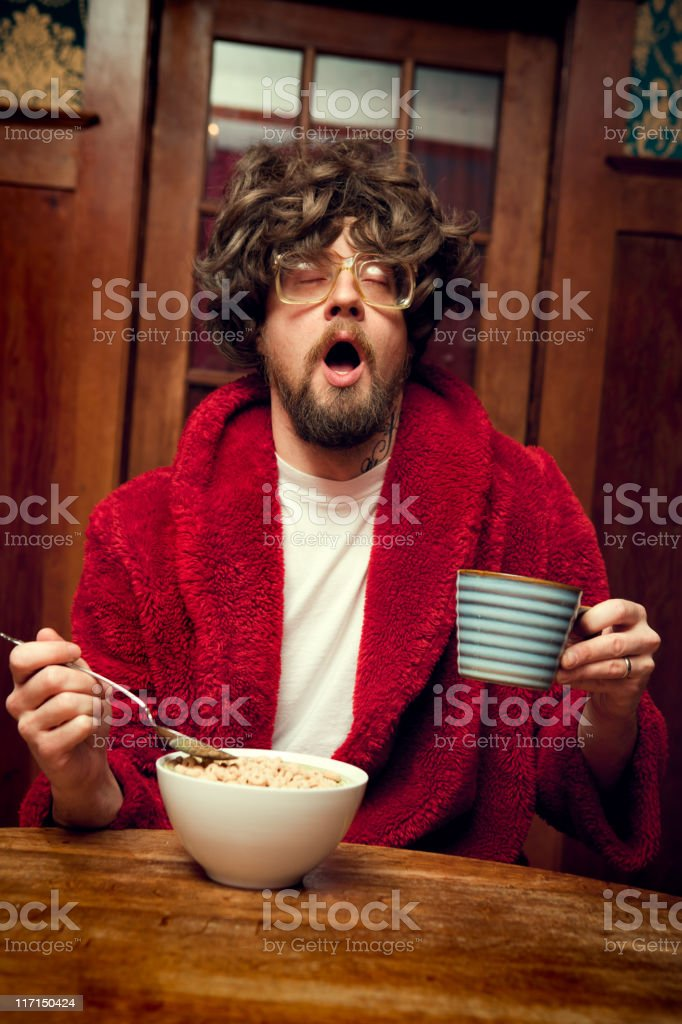 Tired Nerd Man Eating Cereal and Yawning stock photo