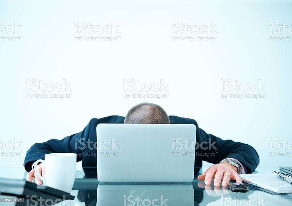 Tired or broken down businessman behind laptop stock photo