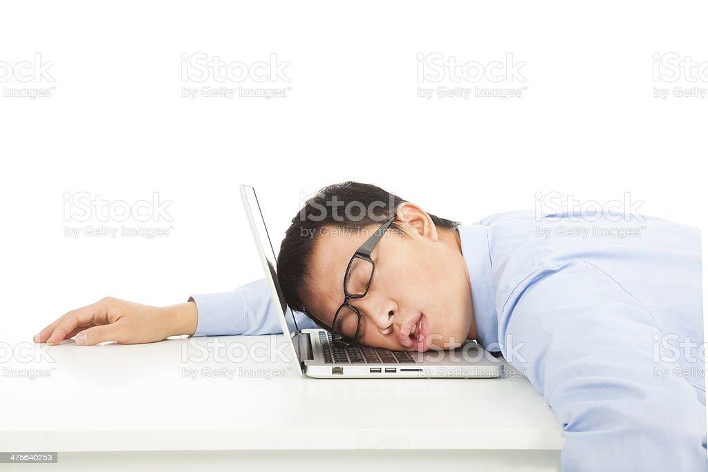 Tired overworked businessman sleeps on laptop stock photo