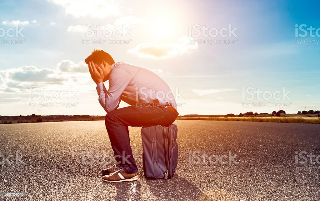 Tired passenger sits on suitcase at airfield waiting for plane stock photo