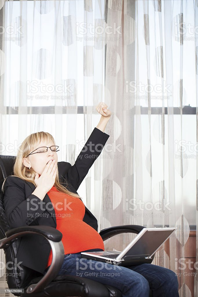 Tired pregnant business woman yawning stock photo