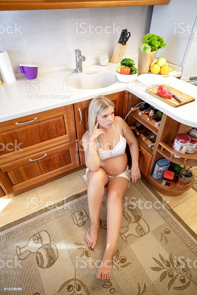 tired pregnant woman sitting on the floor stock photo