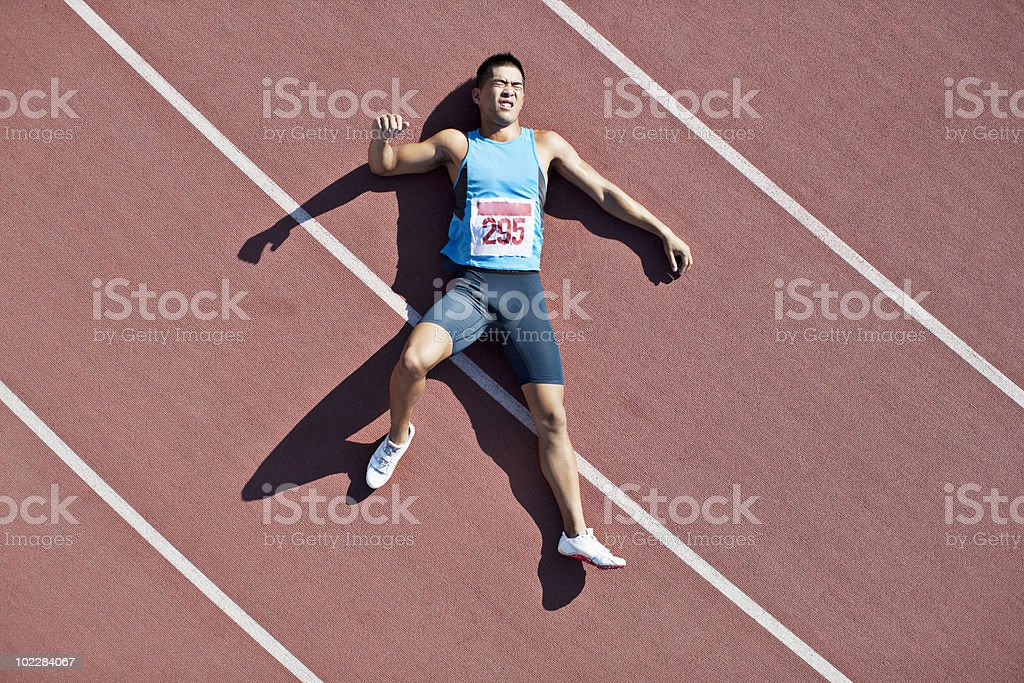 Tired runner laying on track royalty-free stock photo