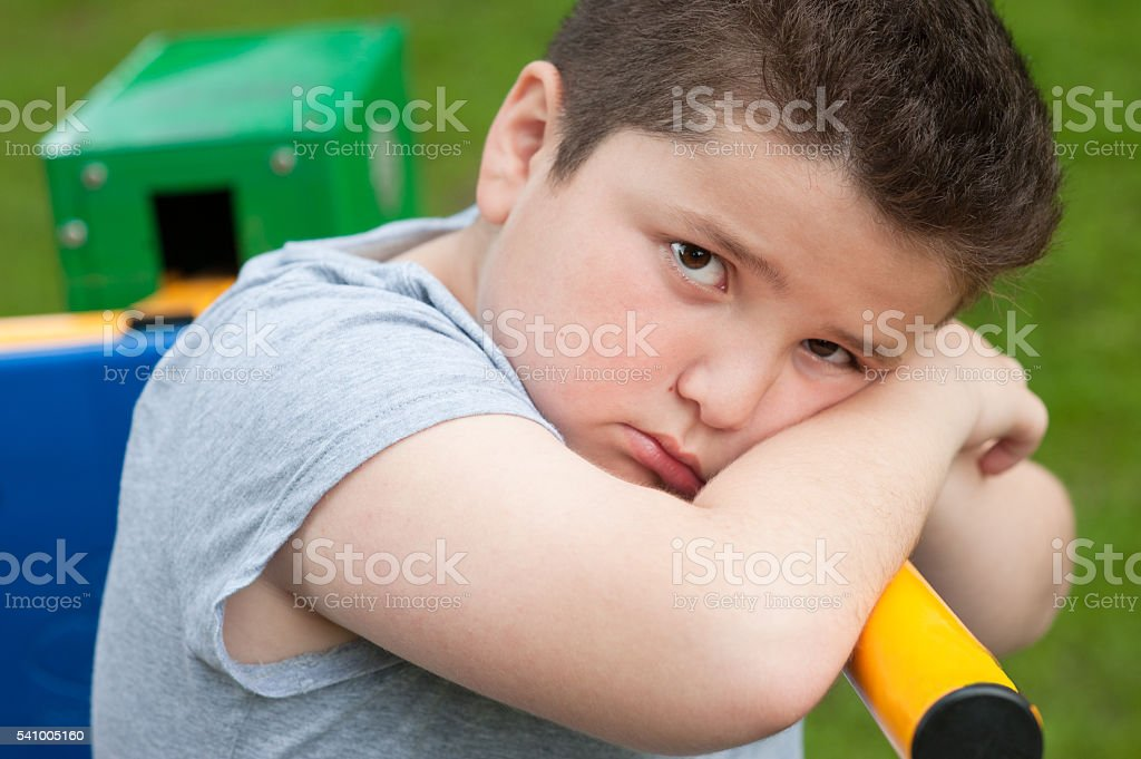 tired sad fat boy sitting on a fitness equipment stock photo