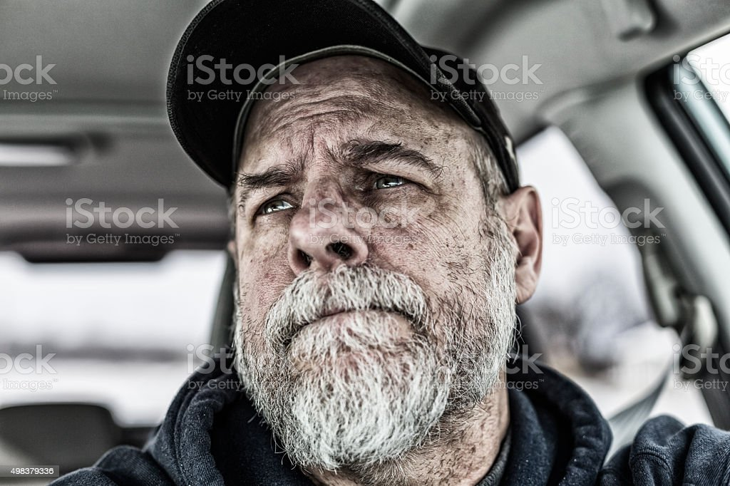 Tired Senior Adult Man Driver Looking In Rear View Mirror stock photo