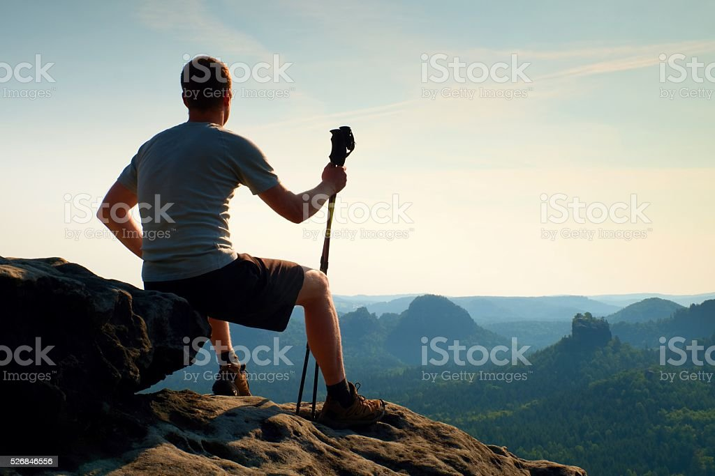 Tired sitting tourist with poles in hand. Sunny spring stock photo