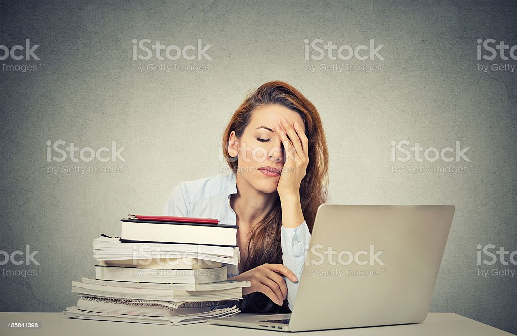 tired sleepy woman sitting at desk with books and computer stock photo