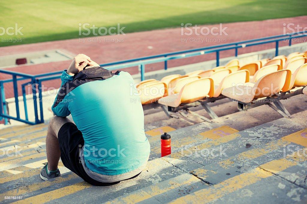 tired sportsman sitting on the stadium stock photo