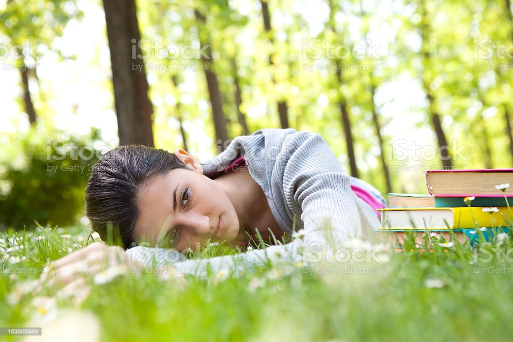 tired student girl lying on grass royalty-free stock photo