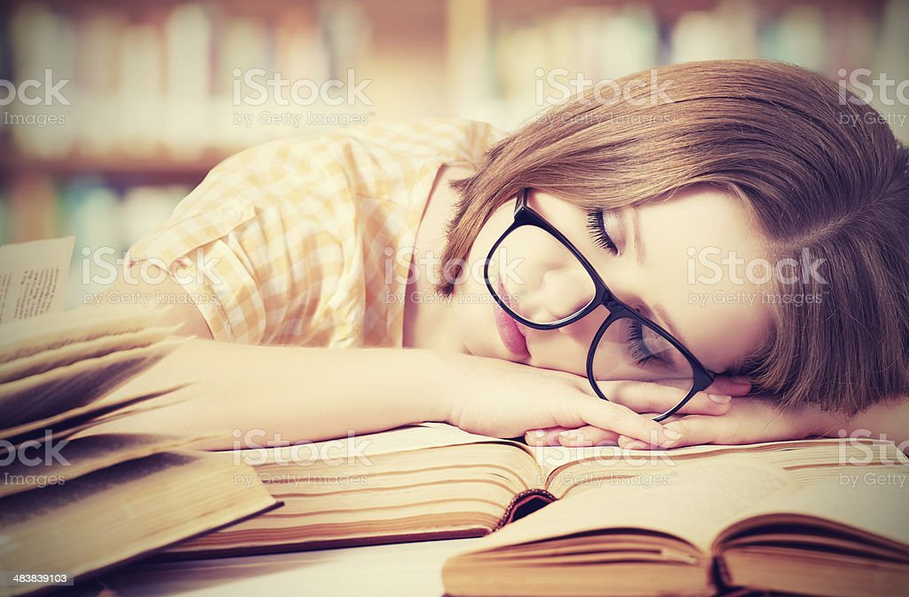tired student girl with glasses sleeping on books in library stock photo